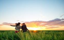 2 подруги бежать в пшеницу на заходе солнца Стоковое Фото
