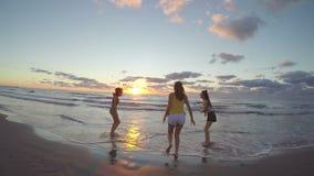 3 подруги бежать на песчаном пляже к морю и играя с их ногами в воде акции видеоматериалы