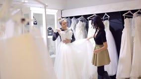 Подруги выбирают мантию свадьбы на bridal магазине видеоматериал