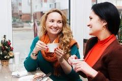 Подруги выпивая кофе в кафе Стоковая Фотография