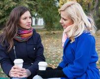 Подруги выпивая кофе outdoors Стоковые Фотографии RF
