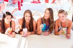 Подруги в коктеилях бара пляжа выпивая Стоковая Фотография