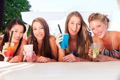 Подруги в коктеилях бара пляжа выпивая Стоковые Фото
