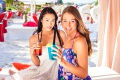 Подруги в коктеилях бара пляжа выпивая Стоковое Изображение
