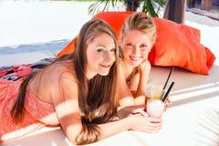 Подруги в коктеилях бара пляжа выпивая Стоковое фото RF