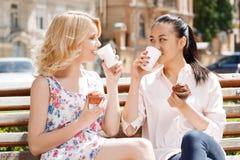2 подруги в парке с кофе и пирожными Стоковая Фотография