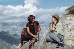 Подруги в фольклорных одеждах смеясь над и имея чаем на m Стоковое Фото