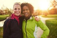 2 подруги в sportswear обнимая в парке Стоковое фото RF
