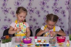 2 подруги девушек получая готовы для пасхи покрасили яичка Стоковые Фотографии RF