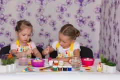 2 подруги девушек получая готовы для пасхи покрасили яичка Стоковое Изображение RF
