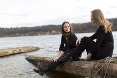 Подруги девушек сидя совместно около реки Природа Стоковое фото RF