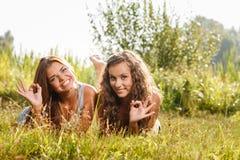 2 подруги лежа вниз на траве Стоковые Изображения