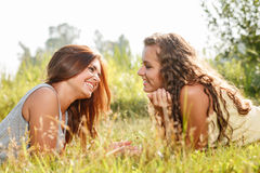 2 подруги лежа вниз на траве Стоковая Фотография