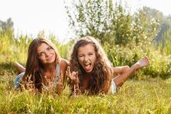 2 подруги лежа вниз на траве Стоковые Фотографии RF