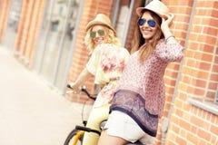 2 подруги ехать тандемный велосипед Стоковая Фотография