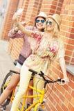 2 подруги ехать тандемный велосипед Стоковое Изображение