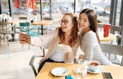 2 подруги делая selfie на кафе Стоковое фото RF