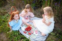 Подруги едят свежие фрукты outdoors Еда девушки и друзей Стоковая Фотография RF