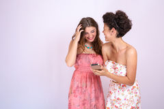 2 подруги имея потеху и удивлены когда они смотрят ваш smartphone Технология, интернет, сообщение Стоковое Изображение RF