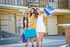 Подруги имея потеху совместно Девушки держа хозяйственные сумки и Стоковая Фотография