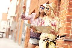 2 подруги используя карту пока едущ тандемный велосипед Стоковое фото RF