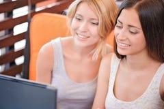 2 подруги используя компьтер-книжку в кафе Стоковые Фотографии RF