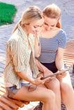 2 подруги используя таблетку в парке Стоковые Фотографии RF