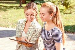 2 подруги используя таблетку в парке Стоковые Фото