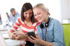 Подруги используя smartphone в классе Стоковые Фотографии RF
