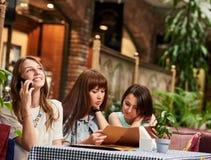 Подруги на кафе с меню Стоковое фото RF