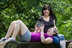 Подруги на парке деля таблетку, горизонтальную Стоковые Фотографии RF