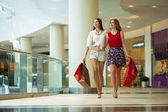 2 подруги на покупках идут на торговый центр с сумками Стоковая Фотография