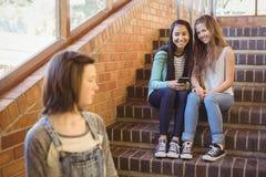 Подруги по школе задирая унылую девушку в коридоре школы Стоковая Фотография
