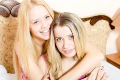 2 подруги привлекательных белокурых молодых женщин красивых в пижамах имея потеху обнимая сидеть на усмехаться белой кровати счас Стоковое Фото