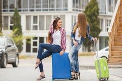 2 подруги при чемоданы ожидая отклонения на авиапорте Стоковое фото RF