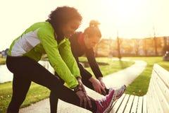 2 подруги протягивая в солнечном парке Стоковые Изображения