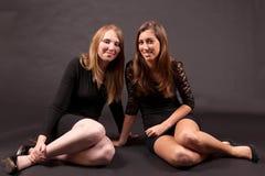 2 подруги сидя и усмехаясь Стоковое Изображение RF