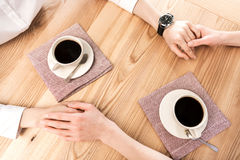 Подруги сидя на кафе и держа руки пока выпивающ кофе Стоковое Фото