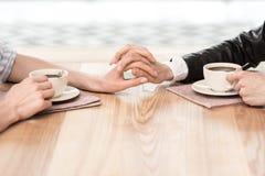 Подруги сидя на кафе и держа руки пока выпивающ кофе Стоковые Фотографии RF