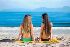 Подруги сидя на пляже Стоковое Фото