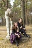 2 подруги сидя около разрушенного памятника искусства sots в старом парке Природа Стоковая Фотография