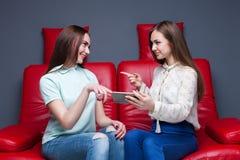 2 подруги смотря изображения на телефоне Стоковая Фотография