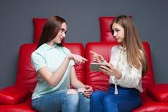 2 подруги смотря изображения на телефоне Стоковые Фото
