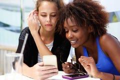 2 подруги смотря мобильный телефон Стоковые Фотографии RF