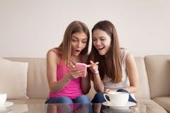 Подруги смотря на смешных фото на мобильном телефоне Стоковое Изображение RF
