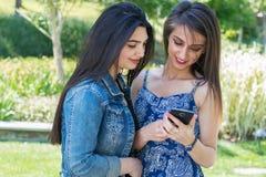2 подруги смотря телефон Стоковое фото RF