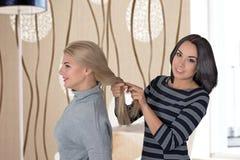 2 подруги стоят в комнате и делают волосы Стоковые Фотографии RF