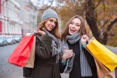 Подруги стоя outdoors и держа хозяйственные сумки Стоковая Фотография