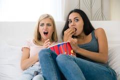 2 подруги с вспугнутым выражением есть попкорн Стоковая Фотография