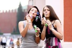 2 подруги с пузырями мыла outdoors Стоковые Фотографии RF